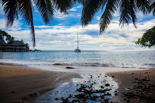 Photo of beach with view on a yacht sailing on the sea.